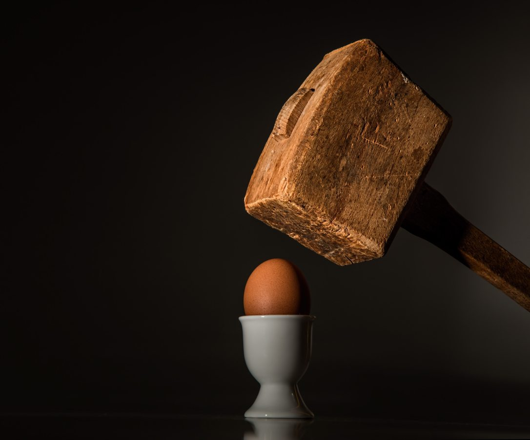 Wooden hammer about to hit fragile egg.