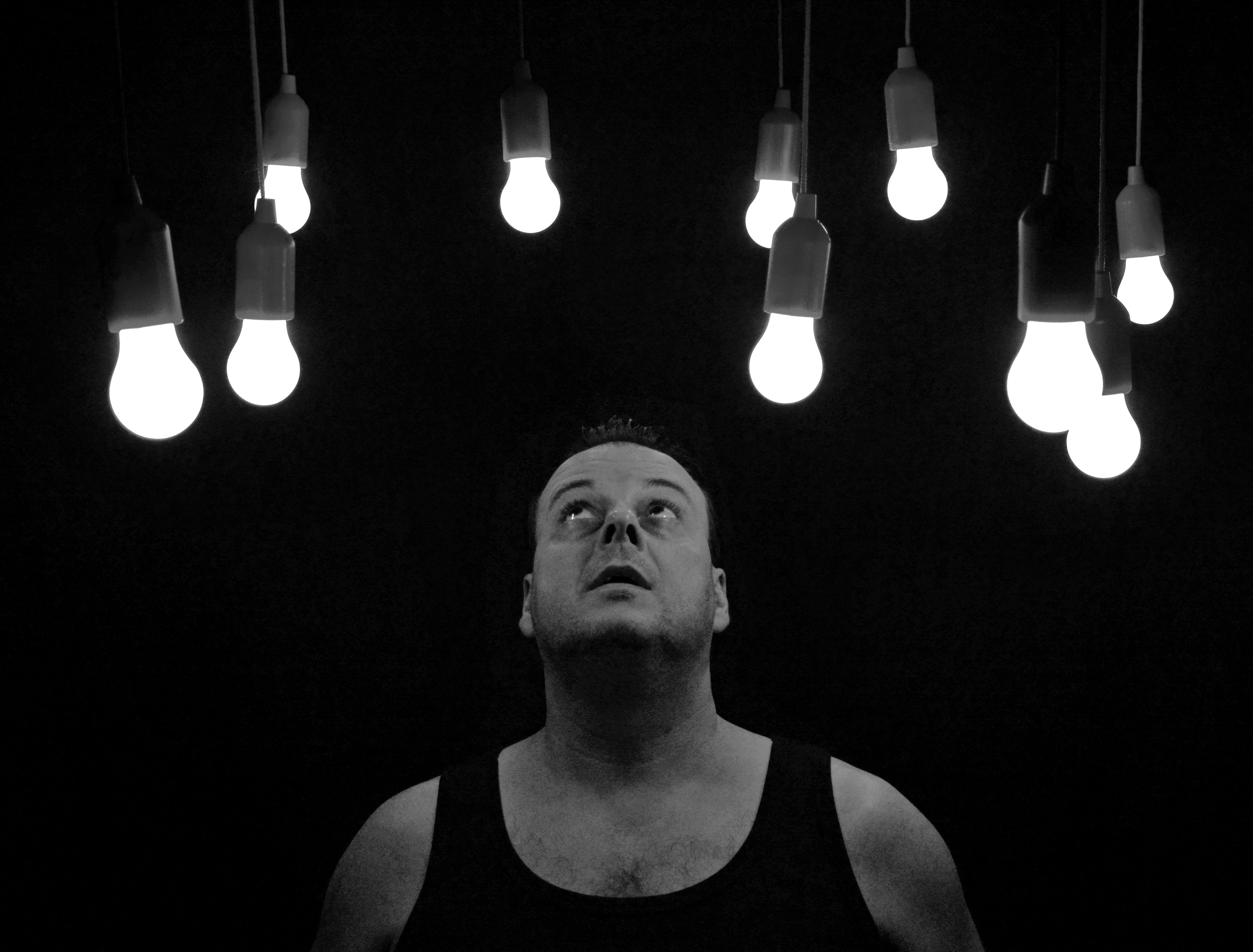 Man is looking up at lights that shine down on him in darkness.